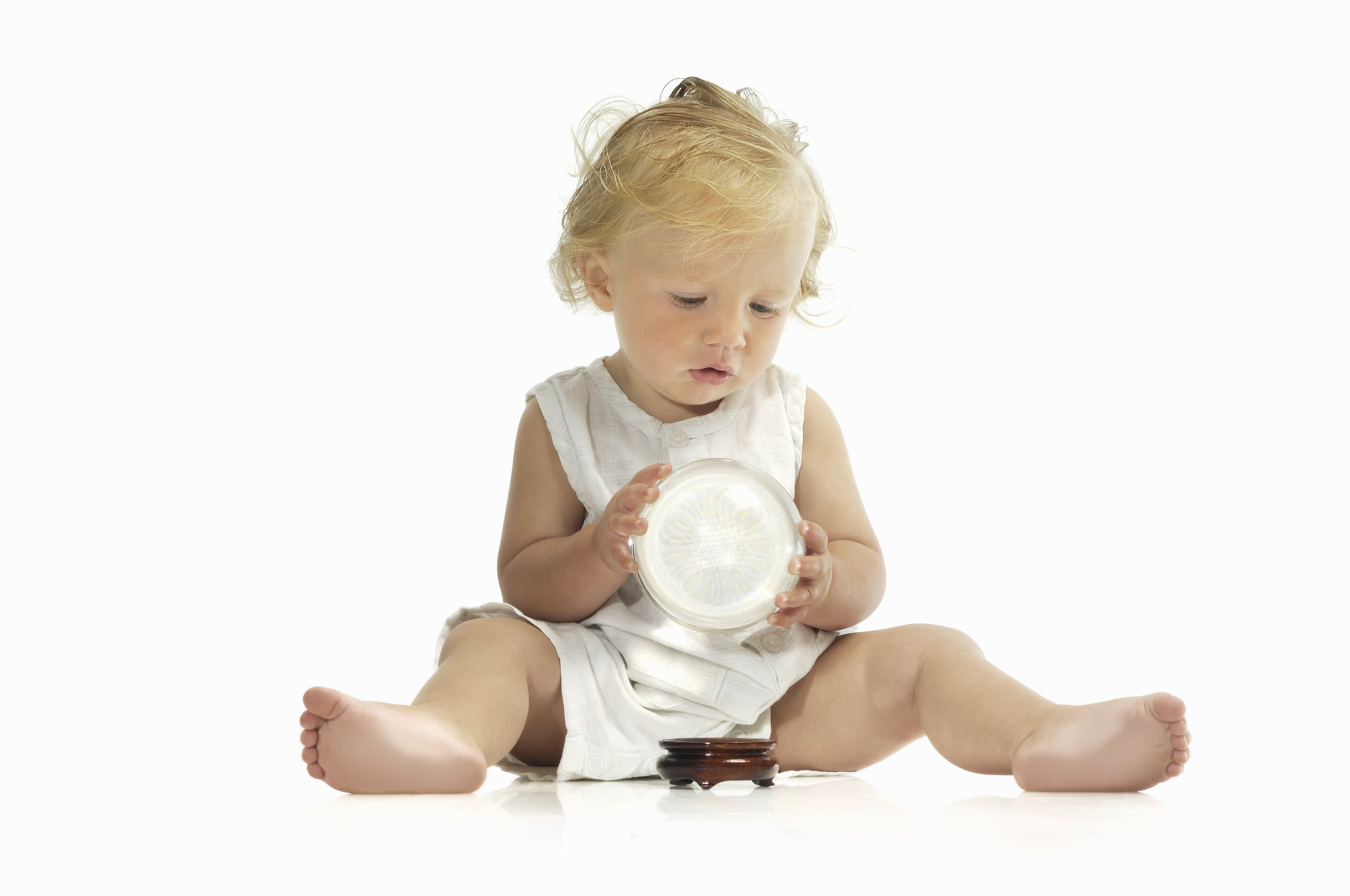 Baby holding and looking into a crystal ball