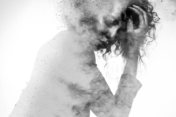 Subtle woman's form in an unhappy pose double exposed with a monochromatic paint splatter photographic effect